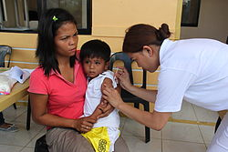 Providing vaccinations to protect against disease after Typhoon Haiyan (11352296333).jpg