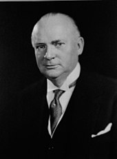 An older white man in a three piece suit, looking at the camera