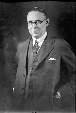 Studio portrait of Richard Gavin Reid. He has an oval, fleshy face with receding hair combed back, a short nose, small shaply mouth. His expression is quizzical and he is compressing a smile. He wears round horn-rimmed glasses and has his hands in the jacket pockets of his neat three-piece suit.