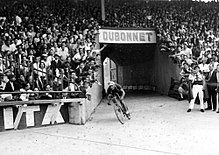 A cyclist entering a crowded stadium.