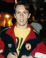 A photograph of a man with short brown hair. He is wearing a black tracksuit top with red trim over a yellow shirt.