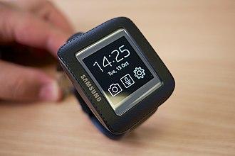 Samsung Galaxy Gear - A Galaxy Gear in its USB charging cradle, displaying a digital clock