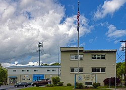 "A buff-colored two-story flat-roofed building under a blue sky with clouds. To the left rear is a garage and a cell-phone tower. In front is a flagpole and a large wooden sign reading ""Col. Roger B.C. Donlon Town Hall""."