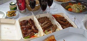 Ćevapi - Ćevapčići are shown on the right in this example of Serbian cuisine.