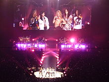 Five ladies are standing in front of a stage and a closeup of them is being projected onto a large screen behind them. There is pink-coloured lighting on the stage.