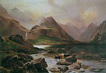 Montañas altas y rocosas se elevan sobre un pequeño lago, más allá del cual una cascada cae en cascada desde las alturas.  El ganado marrón y negro se encuentra junto a los márgenes de los lagos, iluminado por la pálida luz del sol que se filtra entre las nubes.
