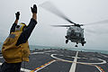 Signalling an MH-60R Seahawk helicopter from Helicopter Maritime Strike Squadron (HSM) 35 on the flight deck of the littoral combat ship USS Fort Worth (LCS 3).jpg