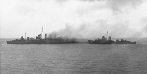 HMAS Canberra (D33) - American destroyers rescuing the surviving crew from Canberra after the Battle of Savo Island. In the billowing smoke, USS Patterson is approaching Canberra from astern.