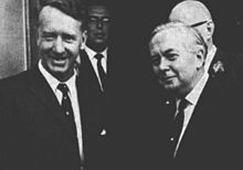 A black-and-white photograph of two middle-aged men in dark-coloured suits, looking towards the viewer. The man on the left is tall, thin and dark-haired, and smiles widely. The man on the right is shorter, more stocky and grey-haired. He wears a neutral expression.