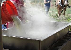 Sweet sorghum - Adding freshly squeezed juice to a simmering pan of syrup on an open fire, much as it was done in the 19th century