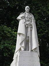 Statue en pierre blanche représentant George V avec une cape et s'appuyant sur une épée.