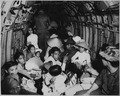 Stunned by the viciousness of a Viet Cong attack on their village, Vietnam war refugees ride an Air Force helicopter to - NARA - 541871.tif