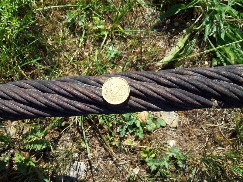 Taille d'un câble de l'ancien transporteur aérien Maxéville-Dombasle exposé à l'entrée de la carrière Solvay de Saint-Germain-sur-Meuse, comparé à une pièce de 20 centimes d'euros.