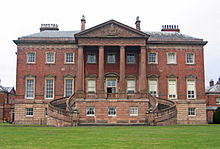 A large Palladian-style house with three storeys, the bottom storey in stone, the upper storeys in brick, with a prominent portico with columns rising to the full height of the building