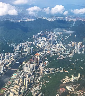 Tai Wai - Aerial view of Sha Tin (foreground), Tai Wai (centre) and the Shing Mun River, looking southwest. The mountains at the back mark the limit between the New Territories and New Kowloon, which is located beyond.
