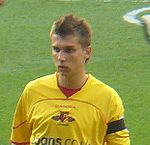 "The head and upper body of young man wearing a yellow top, standing on a grass field. His top features a distinctive red, black and yellow crest, with the word ""Watford"" visible below it."