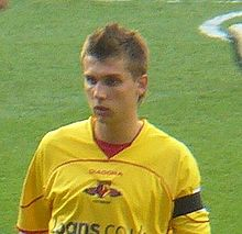 A footballer with spiky hair in a yellow shirt