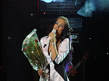 Turunen sings a ballad while holding a bouquet of roses.