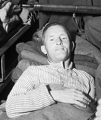 "High treason in the United Kingdom - William Joyce (""Lord Haw-Haw"") was the last person to be tried for treason in the UK, here seen under armed guard in 1945."