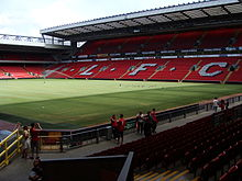 "A two-tiered stand which has red seats, there are also white seats which spell out ""L.F.C. In front of the stand is a field of grass"