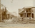 Tornado destruction- man at left in front of small partially destroyed building, and woman at right standing in rubble of heavily damaged building with entire front missing.jpg