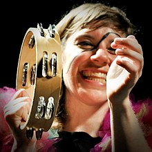 Garbus smiling with make-up on her face, hitting a tambourine