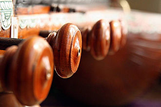 Tuning mechanisms for stringed instruments - Tuning pegs with knobs on a veena.