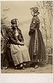 Två unga flickor poserar i dräkter med blommiga jackor och hättor - Nordiska Museet - NMA.0043766.jpg