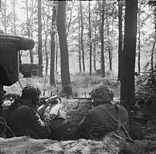 Two men armed with Sten guns, facing away from the camera in woods