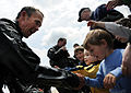 U.S. Air Force Master Sgt. Don Currier, a pararescueman with the 38th Rescue Squadron, greets children at the Virginia Beach boardwalk in Virginia April 22, 2009, after jumping from a C-130 Hercules aircraft 090422-F-IO684-004.jpg