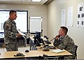 U.S. Army Staff Sgt. Dusty Capshew, left, and Capt. Caleb Emde, both with the Oklahoma Army National Guard, discuss vehicle maneuvers in the Emergency Operations Center (EOC) in Norman, Okla., May 27, 2013 130527-Z-TK779-060.jpg