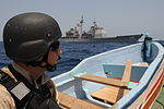 U.S. Navy Cryptologist 3rd Class Vincent Luke, a member of a visit, board, search and seizure team from guided-missile cruiser USS Anzio (CG 68), watches from the deck of a dhow while Anzio sails by Oct. 8 091008-N-PN943-130.jpg