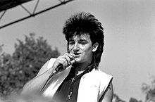 A black and white close-up of Bono holding a microphone to his face. Out-of-focus trees are in the background.