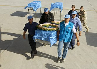 Canal Hotel bombing - United Nations members prepare to load flag-draped metal transfer cases carrying the remains of bombing victims from the UN Office of Humanitarian Coordinator for Iraq (UNOHCI).