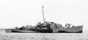 A warship facing right in dazzle camouflage