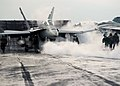 US Navy 031203-N-9742R-002 As steam from a previous launch billows out of the catapult track, flight deck personnel hustle to prepare an F-A-18 Hornet.jpg