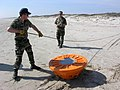 US Navy 050126-D-2006A-003 Two French Explosive Ordnance Disposal (EOD) Navy personnel assigned to the Clearance Diving Team (CDT) Atlantic remove the line from the practice buoy after its beaching on Padre Island, Texas.jpg