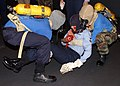 US Navy 050731-N-3891T-019 Airmen Nathanyu Grider and Sean Dixon execute a two man carry, while transporting a simulated casualty during a general quarters (GQ) drill in hangar bay two aboard the Nimitz-class aircraft carrier U.jpg