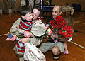 US Navy 060819-N-1924T-001 Hospital Corpsman 2nd Class Misty Racquer embraces her son, as husband looks on with their daughter.jpg