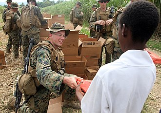22nd Marine Expeditionary Unit - A Marine assigned to Battalion Landing Team, 3rd Battalion, 2nd Marine regiment hands humanitarian ration at an aid distribution site in Leogane, Haiti.