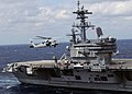 US Navy 100303-N-3885H-172 An MH-60S Sea Hawk helicopter flies alongside USS George H.W. Bush (CVN 77).jpg