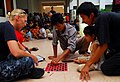 US Navy 100623-N-4044H-047 Religious Programs Specialist 1st Class Jennifer Snow, assigned to the Military Sealift Command hospital ship USNS Mercy (T-AH 19), plays checkers with church members during a community service event.jpg