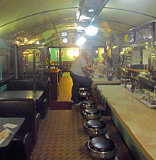 A long, narrow room with a counter and stools on the right at which two men are sitting and standing in the middle with a woman behind the counter a little further on. On the right are tables in booths. Above is a gently vaulted blue-green ceiling