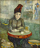 A woman sits in contemplation at a table in a cafe