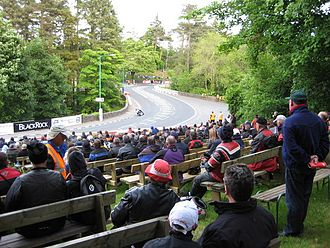 Braddan Bridge - Historical seated area in church grounds, with a TT rider approaching from the first part of the 'S' bend in the distance