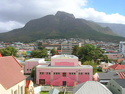 The southern part of Woodstock, seen from the northern end, with Devil's Peak in the background. The pink building in the foreground is the town hall.