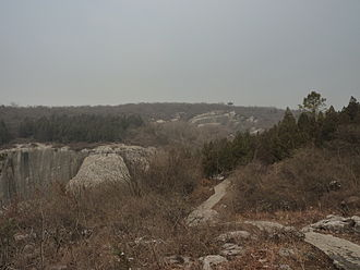 Yangshan Quarry - An overall view of the quarry site from a walking trail. The stele base, center left; the stele body, and the stele head in front of it, near the horizon, a bit right of center