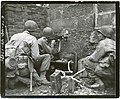 111-SC-195505 - PFC Victor Henry, Pontotoc, Miss., fires his machine gun through a hole in a wall, at Germans in a barn 300 yards away, beyond Kohlscheid, Germany. He is flanked by two of his buddies.jpg