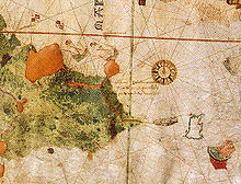 An old, hand-drawn map with a large compass rose on the right side and a coastline drawn on the left side with writing occupying the center