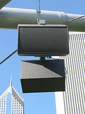 A round, grey metal tube with two dark grey rectangular boxy speakers hanging from it. In the background are the tops of two skyscrapers.